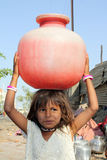 Little Girl Carrying Water. A poor Indian girl carrying water to her home in a red plastic pot, due to scarcity of drinking water to poor people in India Stock Images
