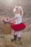 Little girl carrying wicker basket  Royalty Free Stock Photo