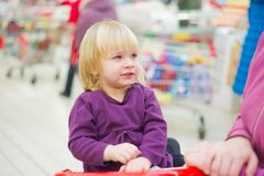 Little girl on cart in supermarket with mother stock photography