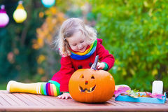 Little girl carving pumpkin at Halloween Royalty Free Stock Images