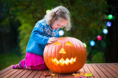 Little girl carving pumpkin at Halloween Royalty Free Stock Photography