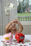 Little girl, cash and piggy banks. Money is falling around a little girl with two piggy banks Royalty Free Stock Photos