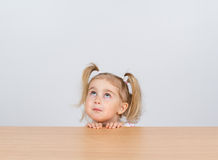 Little girl in casual clothes looking up and thinking Stock Photography