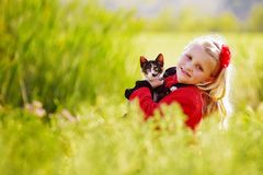 Little girl and cat. A beautiful young Caucasian girl holding her little cat and smiling with friendly facial expression while sitting in a green field Royalty Free Stock Images