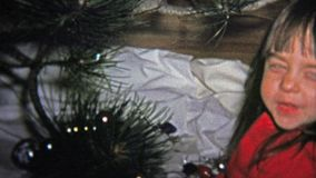 1973: Little girl and cat decorating a Christmas tree with glass ornaments. stock footage