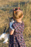 Little girl with a cat in the hands Stock Photos