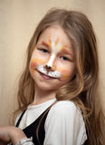 Little girl with cat painting makeup portrait Stock Image
