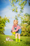 Little Girl and cat play on a green meadow in spring beautiful d. Ay on a farm Royalty Free Stock Photo
