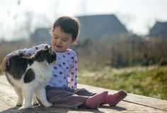 Little Girl and cat play outside near the house Royalty Free Stock Image