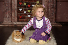 Little girl with cat. Little girl with a red cat Royalty Free Stock Images