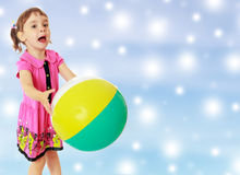 Little girl catches the ball. Emotional little girl with pigtails on the head , in a pink dress. Girl catches with hands a large, inflatable striped ball.On new Stock Images