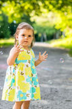 Little girl catches bubbles Royalty Free Stock Photos