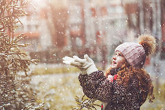 Little girl catches falling snowflakes. Child enjoy first snow in christmas holiday. Toning instagram filter stock photography