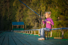 Little girl catches fishing rod Royalty Free Stock Photography