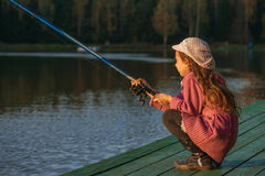 Little girl catches fishing rod Royalty Free Stock Images