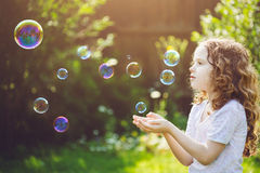 Little girl catches soap bubbles Stock Photos