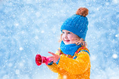 Free Little Girl Catching Snow Flakes Stock Photography - 47155502