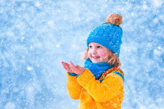 Little girl catching snow flakes Stock Photo