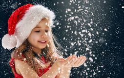 Little girl catching snowflakes Stock Images