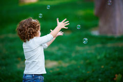 Little girl catching soap bubbles in the park Royalty Free Stock Images
