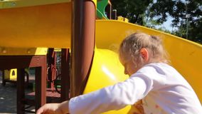 Little Girl On The Kid Slide. Little girl caucasian white european 5 years old on the kid slide at the playground outdoors stock footage