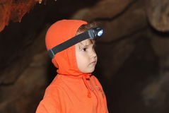Little girl in a cave. Portrait with little girl in a cave with flashlight Stock Photo