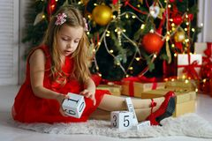 Little girl celebrates Christmas. Little girl in a red dress is sitting on a rug next to dice toys. Christmas tree with ornaments in the background. Happy royalty free stock photo
