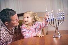 Hanukkah: Girl And Parent Light Hanukkah Candles Together stock photos