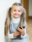 Little girl with cell phone indoors Royalty Free Stock Photo
