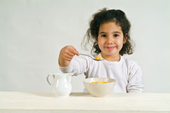 Little girl with cereals. Little girl holding a spoon with cereals Royalty Free Stock Photos