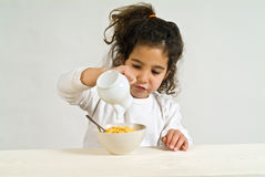 Little girl with cereals. Little girl holding a spoon with cereals Royalty Free Stock Images