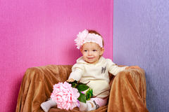 Little girl in the chair with flowers Royalty Free Stock Photography