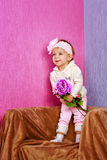Little girl in the chair with flowers Stock Photos