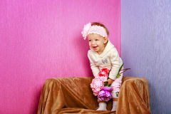 Little girl in the chair with flowers Royalty Free Stock Images