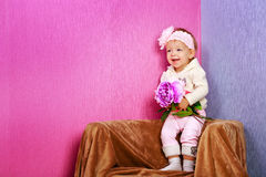 Little girl in the chair with flowers Stock Photo