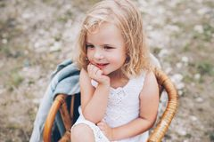 Little girl in a chair outdoors. Happy little girl in a chair outdoors royalty free stock photos