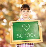Little girl with chalkboard on autumnal background Royalty Free Stock Images