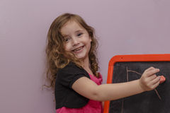 Little girl with chalkboard Stock Image