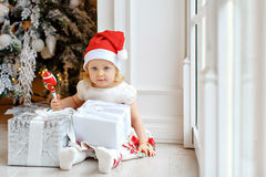 Little girl charming blonde in a Santa hat, smiling and sitting Stock Photo