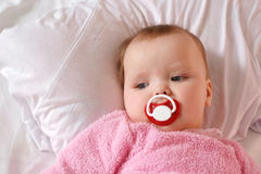 Little girl with a charming pacifier lying Royalty Free Stock Image