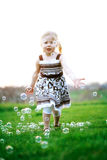 Little girl chasing bubbles. Pretty little blonde girl chasing and popping bubbles in backyard during summer evening stock photography