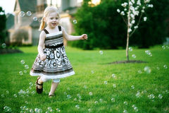 Little girl chasing bubbles. Pretty little blonde girl chasing and popping bubbles in backyard during summer evening stock images