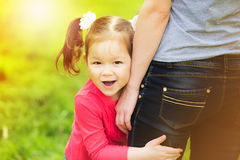 Little girl cheerfully hugging leg of mother. Mom and child having fun outdoors. Happy family portrait at sunny background Royalty Free Stock Image