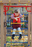 Little girl cheerfully smiles on ladder. Playground in sunny autumn day Stock Photos