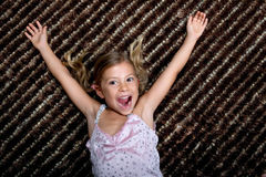 Little girl cheering with delight. Pretty little girl lying on a rug and cheering with delight royalty free stock photography