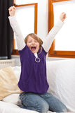 Little girl cheering on sofa Stock Photography