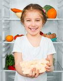 Little girl  against a refrigerator Royalty Free Stock Photo