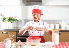Little girl chef breaks an egg. Ttle girl chef breaks an egg to make dough in the kitchen at home stock photo