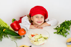 Little girl chef is going to prepare a salad isolated Stock Images