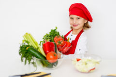 Little girl chef is going to prepare a salad isolated Royalty Free Stock Photos